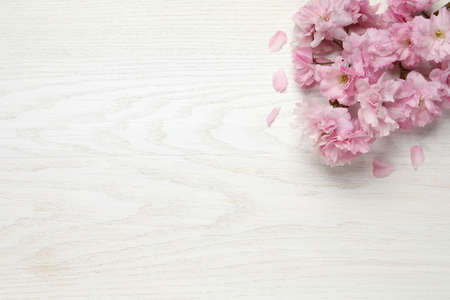 Beautiful sakura tree blossoms on white wooden table, flat lay. Space for text Stock fotó
