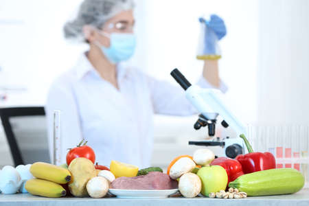 Fresh vegetables, fruits, meat on table and scientist proceeding quality control in laboratory