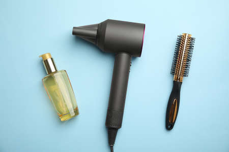 Hair care product, dryer and round brush on light blue background, flat lay Reklamní fotografie