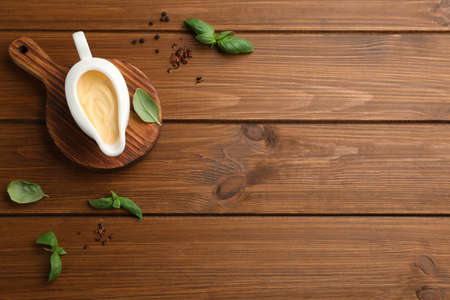Tasty sauce in gravy boat, basil leaves and spice on wooden table, flat lay. Space for text