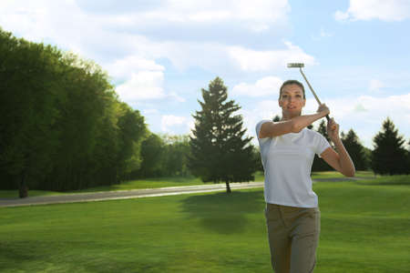 Beautiful woman playing golf on green course, space for text