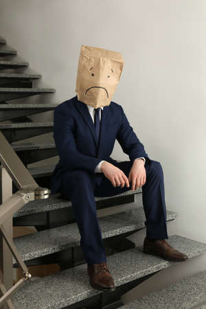 Man wearing paper bag with drawn sad face indoors Standard-Bild