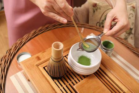 Master preparing matcha drink at wooden table, closeup. Tea ceremony Standard-Bild