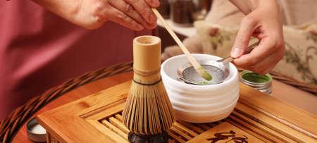 Woman preparing matcha drink at wooden table, closeup. Tea ceremony