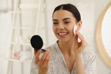 Beautiful young woman applying face powder with puff applicator in bathroom at home