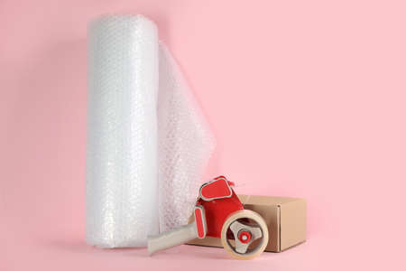 wrap roll, tape dispenser and cardboard box on pink background, space for text