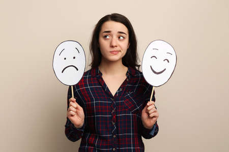 Woman with sad and happy paper faces on beige background Banque d'images