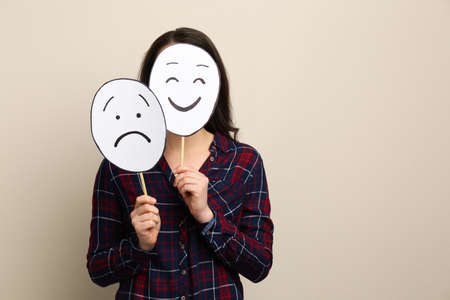 Woman with sad and happy paper faces on beige background. Space for text