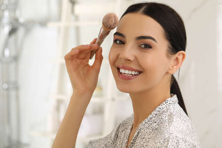 Beautiful young woman applying face powder with brush in bathroom at home