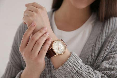 Woman with luxury wristwatch on light background, closeup Stock Photo