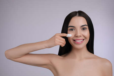 Woman using silkworm cocoon in skin care routine on light gray background. Space for text