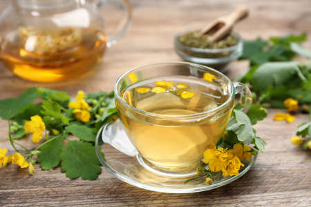 Glass cup of aromatic celandine tea and flowers on wooden table, closeup Banco de Imagens