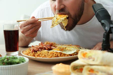 Food blogger eating in front of microphone at table, closeup. Mukbang vlog Imagens