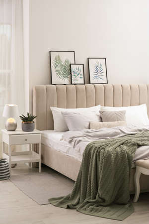 Bed with stylish gray linens near white wall in room Banque d'images