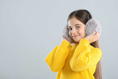 Cute girl wearing stylish earmuffs on gray background. Space for text Reklamní fotografie