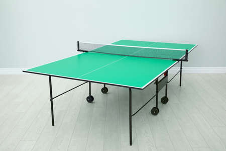 One green tennis table with net indoors