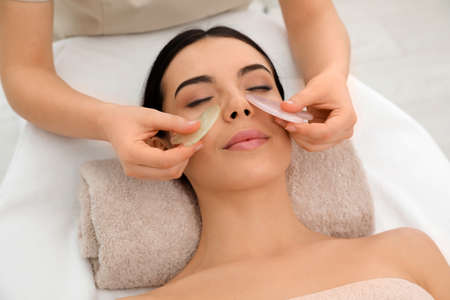 Young woman receiving facial massage with gua sha tools in beauty salon Banque d'images
