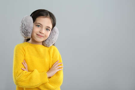 Cute girl wearing stylish earmuffs on gray background. Space for text