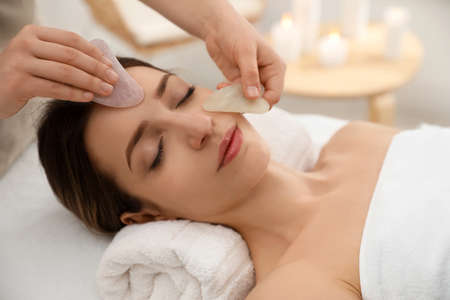 Young woman receiving facial massage with gua sha tools in beauty salon