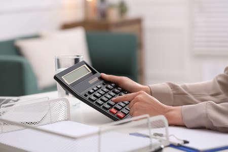 Woman using calculator at table indoors, closeup