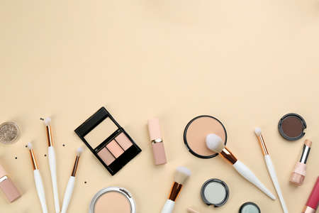 Different makeup brushes and cosmetic products on beige background, flat lay. Space for text Archivio Fotografico