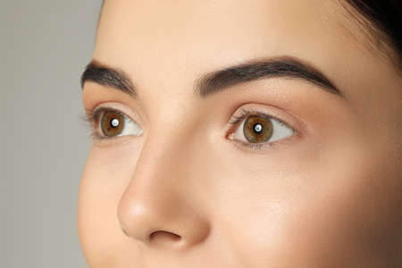 Young woman with beautiful eyebrows on gray background, closeup