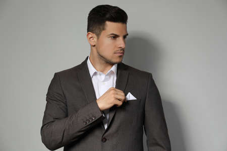 Man fixing handkerchief in pocket of his suit on light gray background