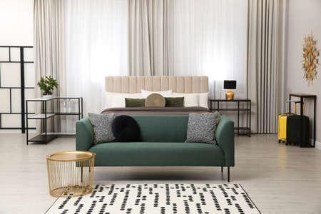 Beautiful hotel room interior with green sofa Фото со стока