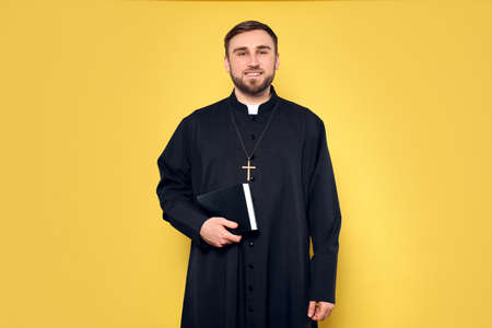 Priest in cassock with Bible on yellow background