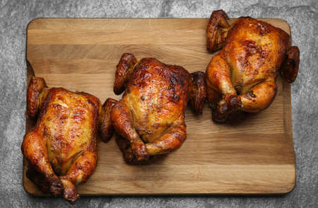 Delicious grilled whole chickens on gray table, top view