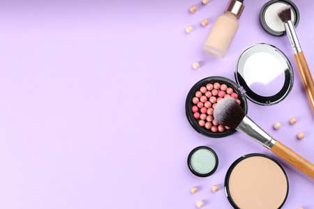 Flat lay composition with makeup brushes on violet background, space for text