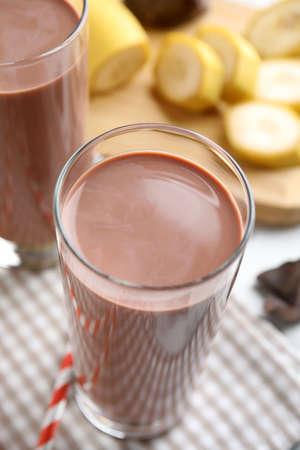 Fresh yummy chocolate milk in glass on table, closeup