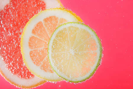 Slices of different citrus fruits in sparkling water on pink background, closeup
