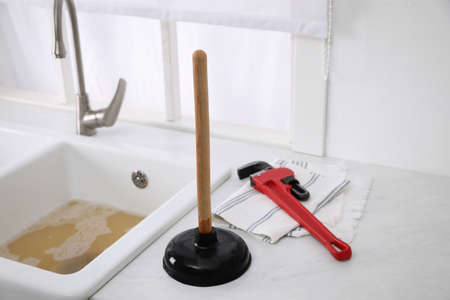Plunger, pipe wrench and towel on kitchen counter near clogged sink