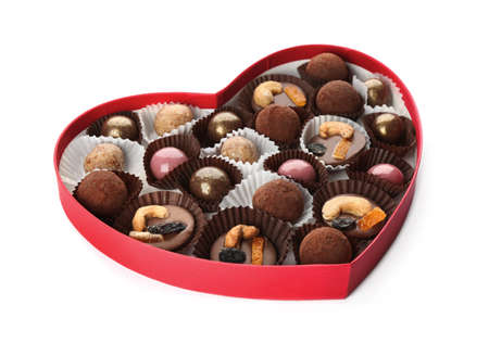 Delicious chocolate candies in heart shaped box on white background
