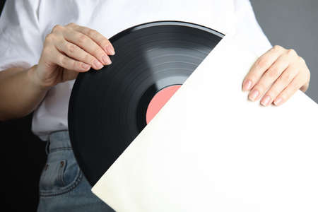 Woman taking vinyl record out of paper sleeve on gray background, closeup 版權商用圖片