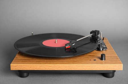 Modern vinyl record player with disc on gray background 版權商用圖片