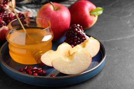 Honey, pomegranate and apples on black table, closeup. Rosh hashana holiday