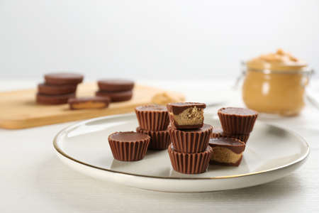 Cut and whole delicious peanut butter cups on white table