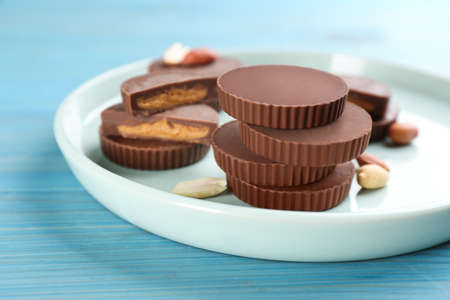Delicious peanut butter cups on light blue wooden table, space for text
