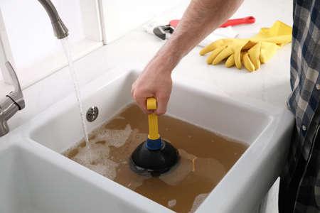 Man using plunger to unclog sink drain in kitchen, closeup 版權商用圖片