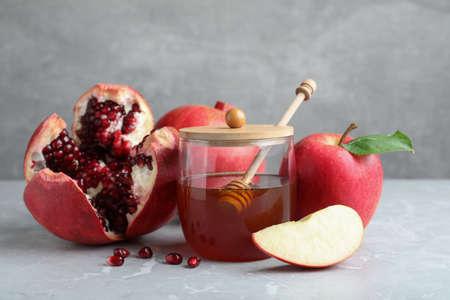 Honey, pomegranate and apples on gray marble table. Rosh hashana holiday
