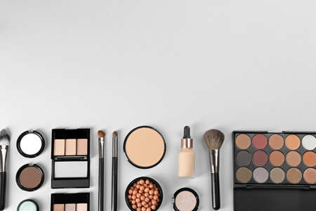 Flat lay composition with makeup brushes on light background, space for text