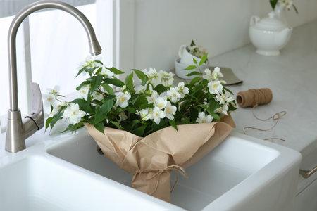 Bouquet with beautiful jasmine flowers in kitchen sink