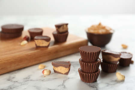 Delicious peanut butter cups on white marble table, space for text