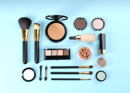 Flat lay composition with makeup brushes on light blue background