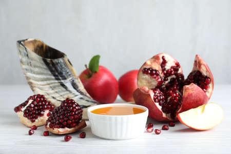 Honey, pomegranate, apples and shofar on white wooden table. Rosh hashana holiday