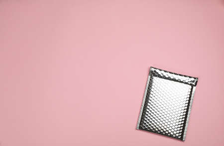 Padded envelope with wrap on light pink background, top view. Space for text