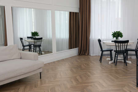 Modern room with parquet flooring and stylish furniture Фото со стока