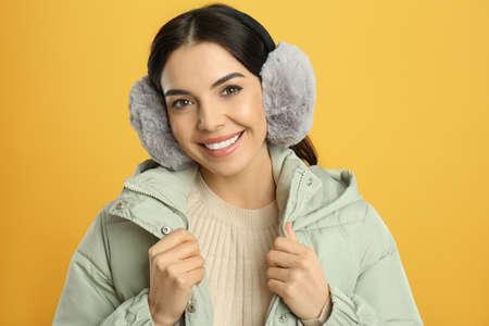 Beautiful young woman wearing earmuffs on yellow background